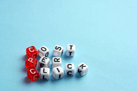 cpc: CPC Cost Per Click written  on dices on blue Stock Photo