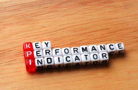 performance: KPI Key Performance Indicator written on cubes on wooden background