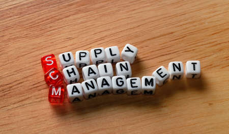 scm: SCM Supply Chain Management written on dices on wooden  background Stock Photo