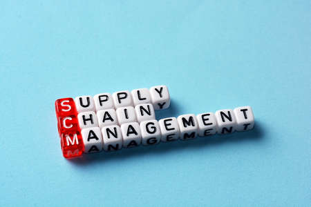 scm: SCM Supply Chain Management written on dices on blue background