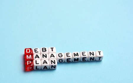 debt management: DMP Debt Management Plan written on cubes on blue background