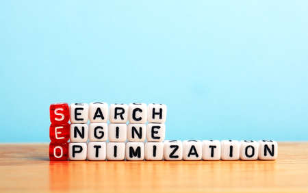 search engine marketing: SEO Search Engine Optimization written on dices  on blue background Stock Photo