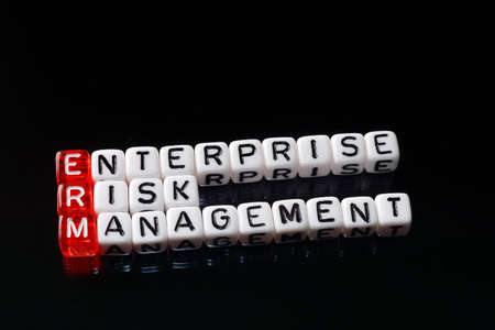 business risk: ERM Enterprise Risk Management writen on dices on black background Stock Photo
