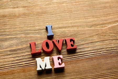 egoistic: I LOVE ME- word made from multicolored   letters on wooden  background warm color Stock Photo