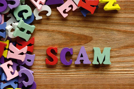 SCAM - words  made from multicolored   letters on wooden  background Stock Photo