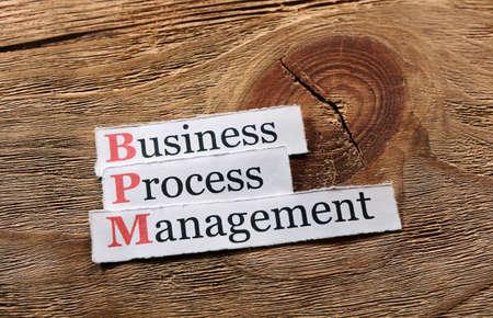 business improvement: BPM business process management on  paper ,wooden background
