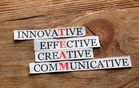communicative: team acronym in business concept, words on cut paper on wood