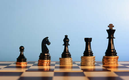Chess pieces on stacked coins against  blue  background ,business concept