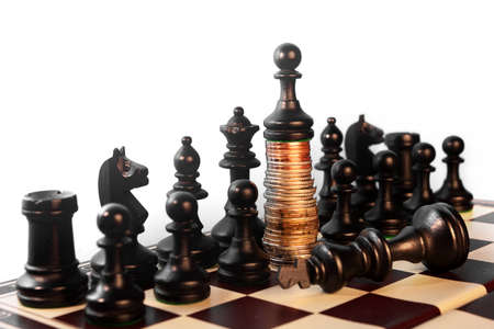 power of the money concept. Chess pawn standing on the money over the king Stock Photo