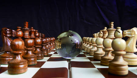 Chess figures against  glass globe . Winner or success  concept.