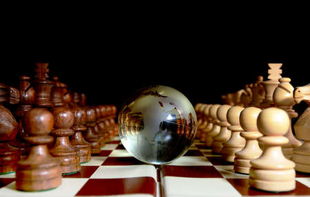 Chess figures against  glass globe . Competition  or success  concept. Stock Photo