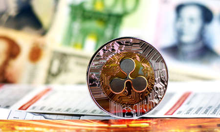 Golden Ripple coin against of different banknotes on background. Cryptocurrency Trading concept . Stock Photo
