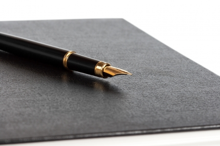 black notebook and the black pen with a gold feather photo