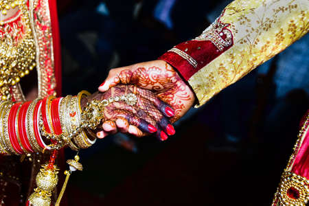 The groom hold hands of bride to come up on the stairs stage, wedding palace during wedding ceremony.  top view. Wedding