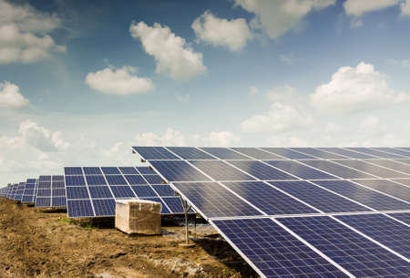 Side view of Installed row of Photovoltaic solar panels / modules at solar power station. Clear sky sunny day clear view. Black cotton soil