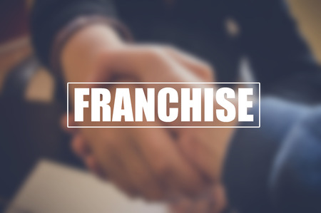 franchise with blurring business men shaking hands background