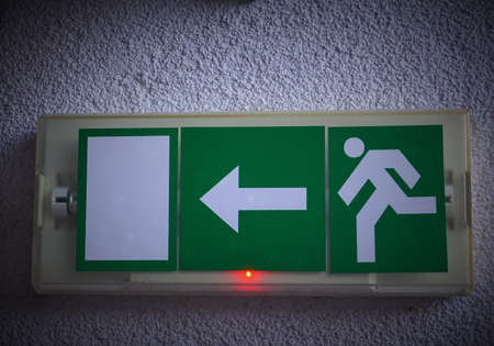 Exit sign with grey background.
