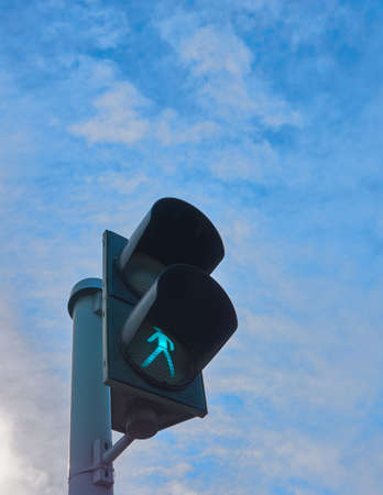 Green traffic light with clouds in background