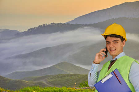 Young engineer with helmet  and clipboard, speaking on mobile phone