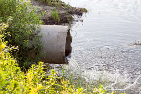 concrete pipe from which water flows which pollute the river Stock Photo