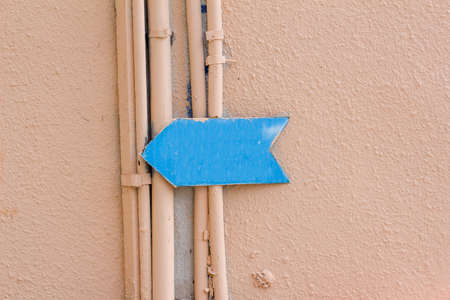 blue arrow: the blue arrow on the yellow wall of the building