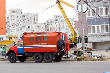 under fire: fire truck with the words technical service in Russian near a house under construction Editorial