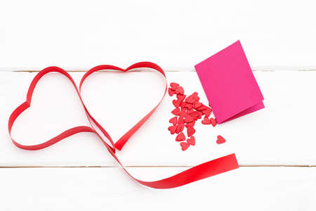 two hearts of red ribbon with a few small hearts and greeting card on white wooden background. romantic love background for Valentines day, birthday, holiday, party, wedding