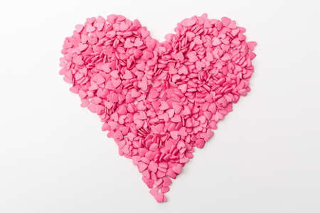 pink heart made of many smaller hearts on a white background. festive background for Valentines day, birthday, holiday Stock Photo