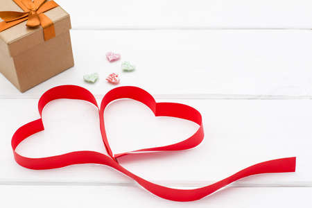 heart made of red ribbon, a few little hearts and gift box on white wooden background. valentines day concept. romantic love background for birthday, holiday, party, wedding Stock Photo