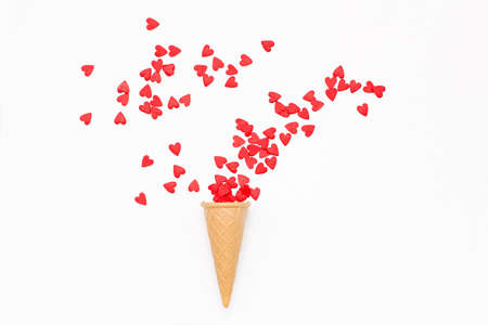 waffle cone and lot of small hearts on a white background. romantic love background for Valentines day, birthday, holiday, party, wedding. Flat lay.