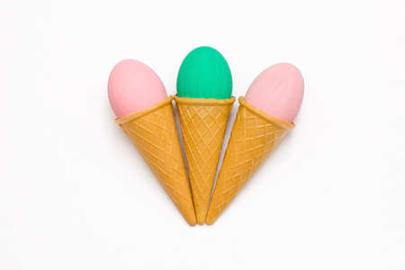 three eggs in waffle cones on a white background. flat lay, Easter decoration concept.