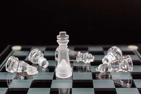chess board: Chess of glass. The king and defeated the opponents pieces on a black background. Minimal business concept.