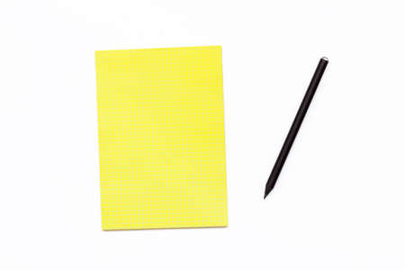 yellow notepad: Black pencil and a yellow Notepad on a white background. Minimal business concept office Desk. Flat lay. Top view.