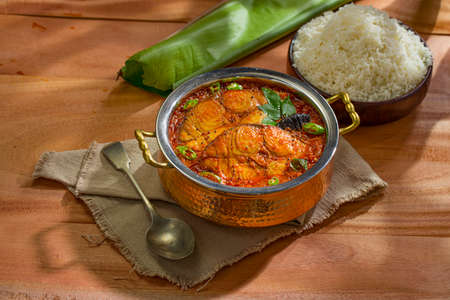 Seer Fish curry, traditional Indian fish curry ,kerala special ,arranged in a copper serving bowl with a bowl of cooked rice and banana leaf for serving food,arranged on wooden textured background,isolated.