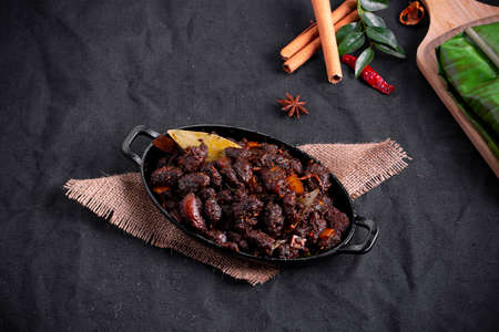 Beef roast or pothu ulartheyadu, kerala special dish arranged in an black table ware and in banana leaf in traditional way placed on a black colour background.