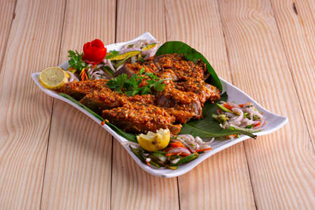 Pomfret masala or meen pollichadu,special kerala dish using spices and arranged in a tableware lined with banana leaf,garnished with salad and lemon slices on white textured background.