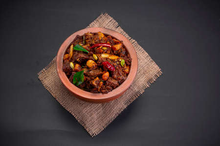 Beef roast or pothu ulartheyadu, kerala special dish arranged in an earthenware in traditional way garnished with coconut pieces on a black colour background. Foto de archivo