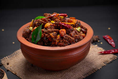 Beef roast or pothu ulartheyadu, kerala special dish arranged in an earthenware in traditional way garnished with coconut pieces on a black colour background.