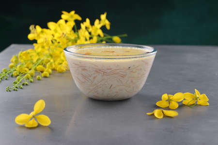 Vermecelli Payasam or Kheer ,South Indian main sweet dish made during special occassions using vermicelli ,milk,sugar and dry nuts and beautifully arranged with golden shower flower in the grey white textured background, selective focus.