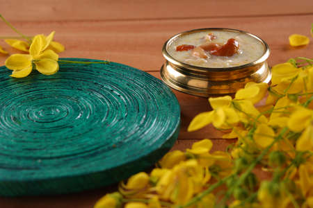 Vermecelli Payasam or Kheer ,South Indian main sweet dish beautifully arranged in a brass vessel with green round base placed near by and golden shower flower in the wooden background, selective focus.