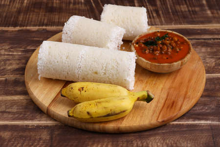 Puttu/Raw rice puttu/Arisi Maavu Puttu with chana curry/ kadala curry-Kerala special breakfast items made using raw rice flour, an ideal combination arranged in a wooden base with banana, on wooden background. Imagens