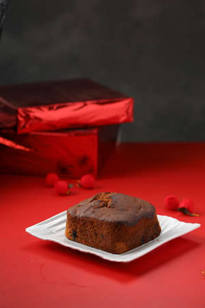 Plum cake, home made delicious christmus cake using raisins ,cashew nuts and dried fruits which is square in shape placed on white tableware with red colour background and gifts just behind the cake.