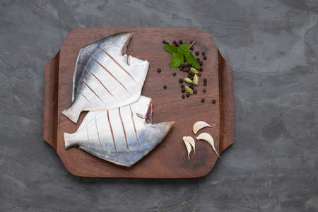 Raw white pomfret,ready to cook pomfret arranged on a wooden board with mint leaves,garlic ,black pepper and cardamom beside it on agrey colour background. Stock Photo