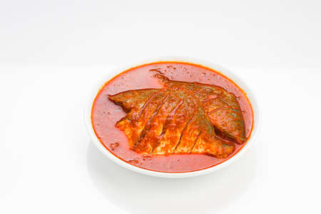 White pomfret masala curry , made in south indian style with thick red gravy and garnished with green chilli,curry leaves and malabar tamarind arranged in a white ceramic bowl with white colour background.