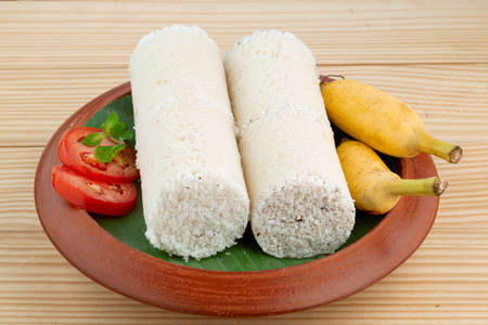 Puttu or White rice puttu -Kerala special breakfast items made using rice flour which is very healthy and arranged in a earthenware with wooden textured background Foto de archivo