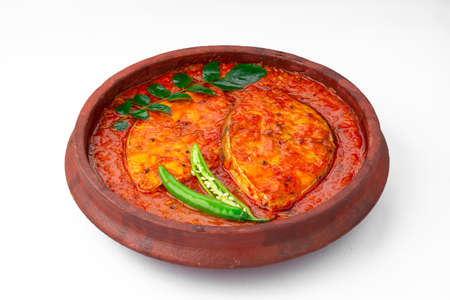 Fish curry_ seer fish , traditional Indian fish curry ,kerala special ,arranged in a white bowl garnished with curry leaves and fresh green chilli on a white background.