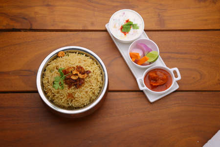 Veg Biriyani , garnished with fried onion ,coriander leaf and fried cashew nut in an antique brass vessel with lemon pickle ,veg salad, raitha and a plate of masala paapad as side dish with wooden texture