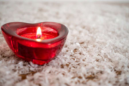 Heart shape with burning candle inside on white snow like background. Valentine Day Concept.