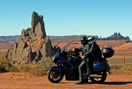wastes: Couple on the motorbike agains the desert landscape background Stock Photo