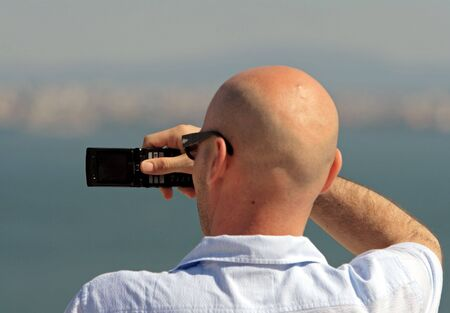 Man taking a picture with a mobile phone. Picture taken in Lisbon  Portugal. photo